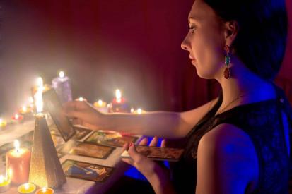 mujer echando las cartas con velas encendidas