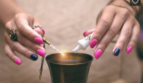 manos de mujer vertiendo gotas en vasija para hechizo
